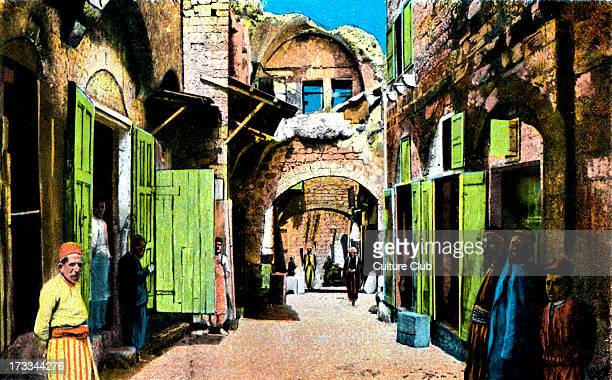 Jaffa Arab quarter Late 1800s early 1900s Shopowners standing outside their shops in narrow streets Published by Cairo Postcard trust