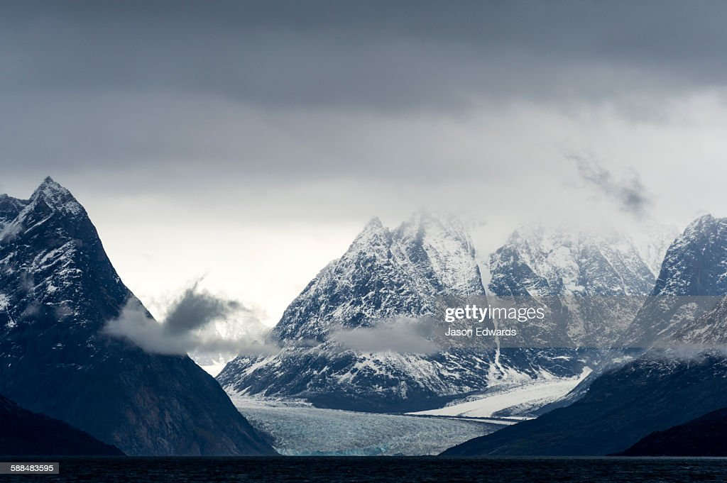 Jagged mountain peaks rise above a glacier in a arctic fjord.