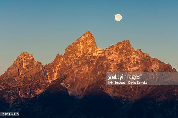 A jagged mountain range in the Grand Teton national park at night, with a full moon in the sky.