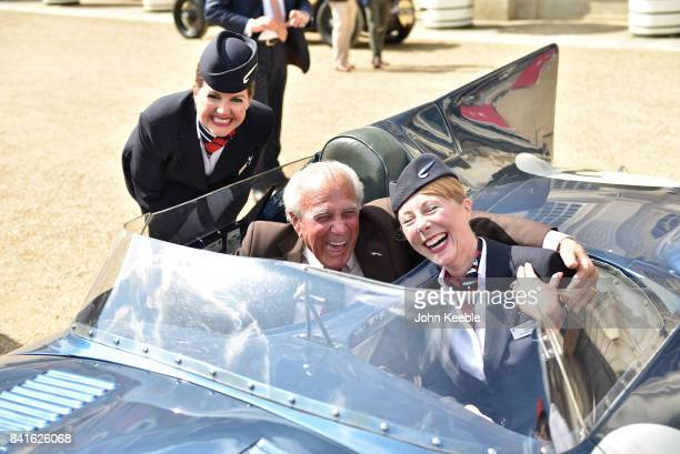 Jaguar team mechanic Ron Gaudion poses with British Airways air stewardesses at the Concours of Elegance at Hampton Court Palace on September 1 2017...