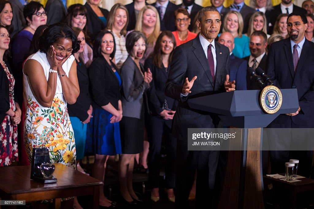 Jahana Hayes (L), a high school history teacher from Waterbury, CT, celebrates winning the 2016 National Teacher of the Year as US President Barack Obama (C) speaks during an event at the White House in Washington, DC, May 3, 2016. / AFP / Jim Watson