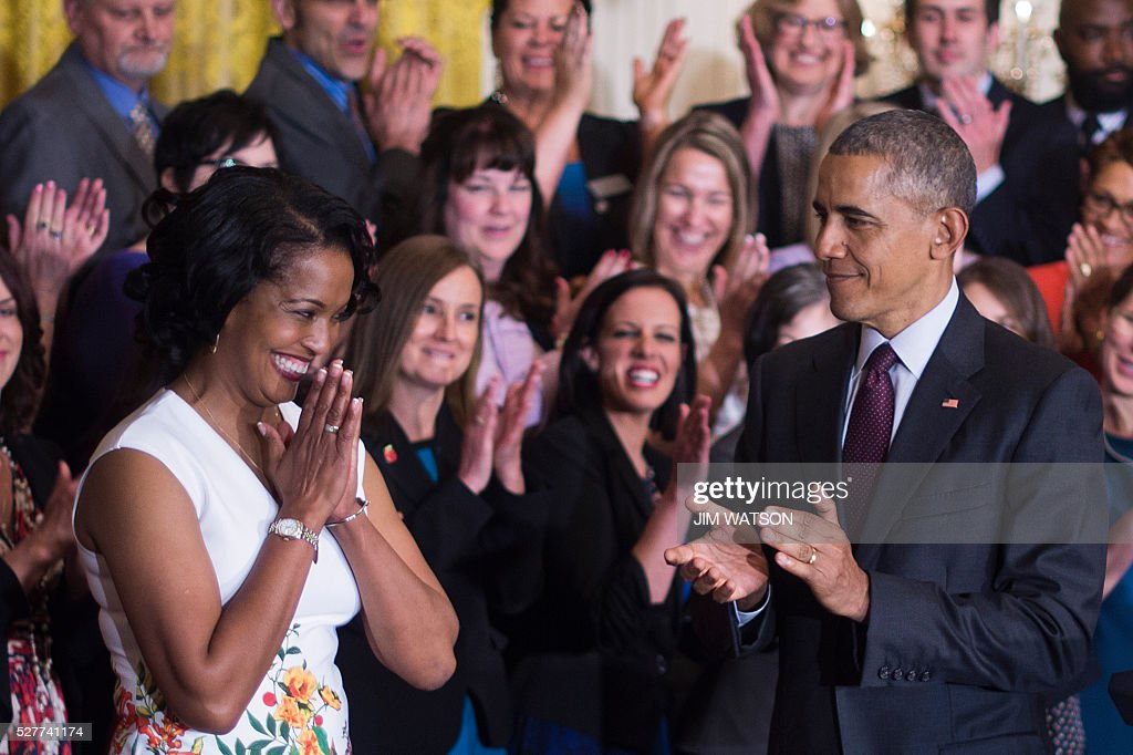 Jahana Hayes (L), a high school history teacher from Waterbury, CT, celebrates winning the 2016 National Teacher of the Year as US President Barack Obama (C) looks on during an event at the White House in Washington, DC, May 3, 2016. / AFP / Jim Watson