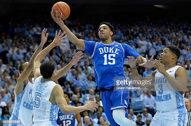 Jahlil Okafor of the Duke Blue Devil drives between defenders Brice Johnson Marcus Paige and Marcus Paige of the North Carolina Tar Heels during...