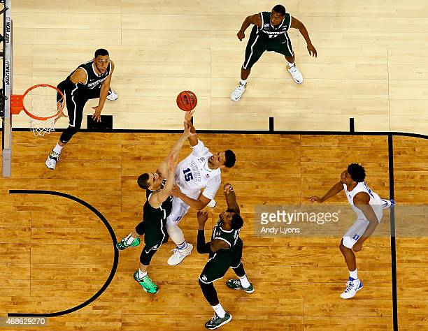 Jahlil Okafor of the Duke Blue Devils drives to the basket against Gavin Schilling and Branden Dawson of the Michigan State Spartans in the second...