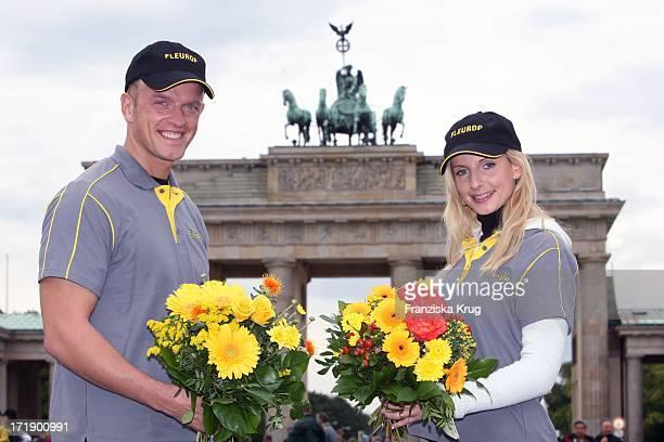 Zum Jubiläum Verteilen Blumenboten Kostenlose Blumensträusse Vor Dem Brandenburger Tor In Berlin