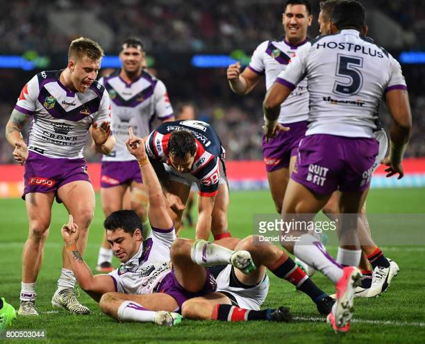 Jahrome Hughes of the Storm celebrates with his team mates after scoring a try during the round 16 NRL match between the Sydney Roosters and the...