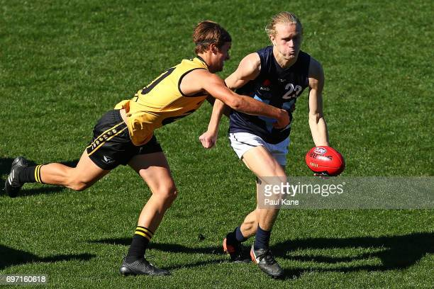 Jaidyn Stephenson of Vic Metro looks to handball against Connor West of Western Australia during the U18 Championships match between Western...