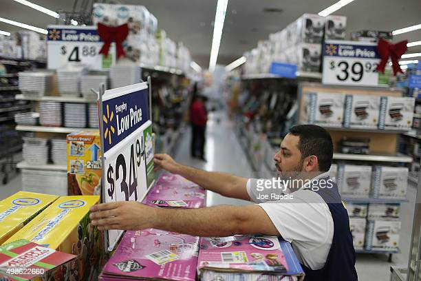Jaime Vado fixes a display in the isle at a Walmart store as they prepare for Black Friday shoppers on November 24 2015 in Miami Florida Black Friday...