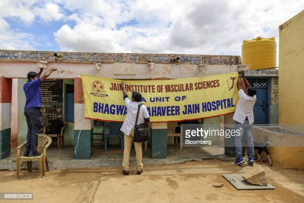 Jain Institute of Vascular Sciences medical staff hang a banner outside a school while setting up a mobile clinic at Pancharala on the outskirts of...