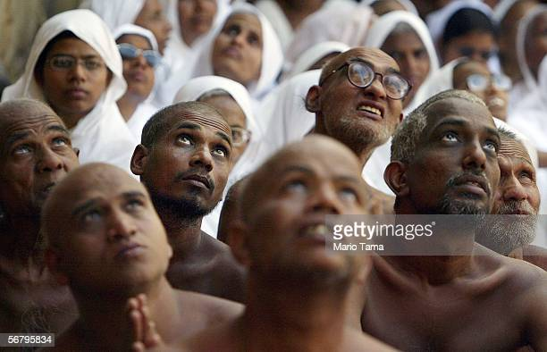 Jain Sadhus and nuns watch holy liquid pour off the monolithic statue of the Jain sage 'Gomateshvara' during the Mahamastak Abhisheka ceremony...