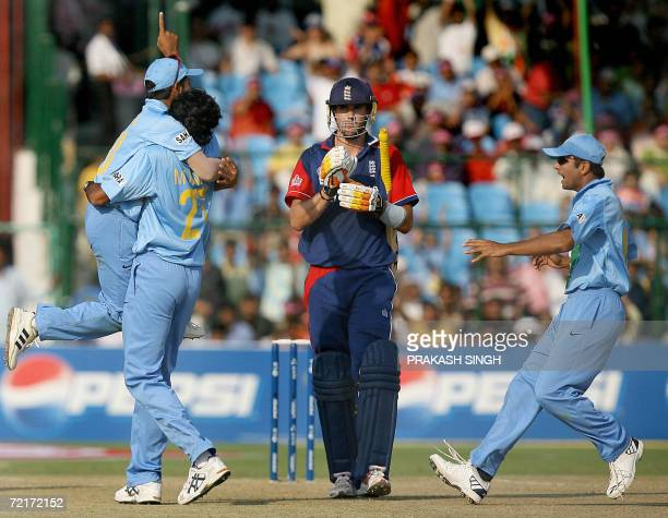 Indian cricketer Munaf Patel celebrates with teammates Suresh Raina and Rahul Dravid after taking the wicket of England batsman Kevin Pietersen...