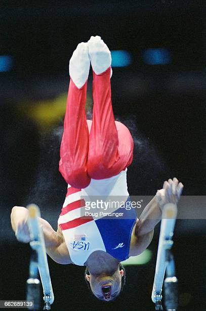 Jair Lynch of the United States performs his routine during the Men's Parallel Bars event of the XXVI Summer Olympic Games on 29 July 1996 at the...