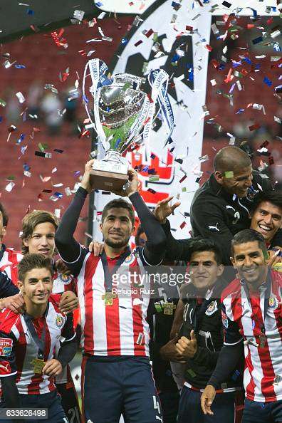 Jair Pereira of Chivas celebrates with the trophy and teammates after a friendly match between Chivas and Boca Juniors at Chivas Stadium on February...
