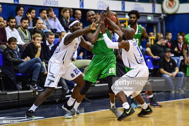 JaJuan Johnson of Darussafaka Dogus Istabul clings on to the ball despite the attentions of Gavin Ware of Levallois and Petr Cornelie of Levallois...