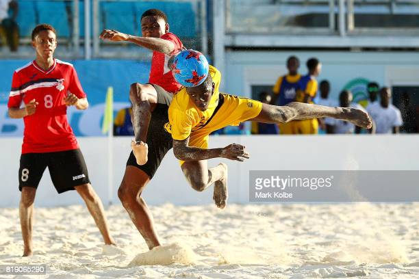 Jajuan Williams of Antigua Barbuda heads at goal under pressure from Anderson Peters of Trinidad Tobago during the Beach Soccer match 2 between...