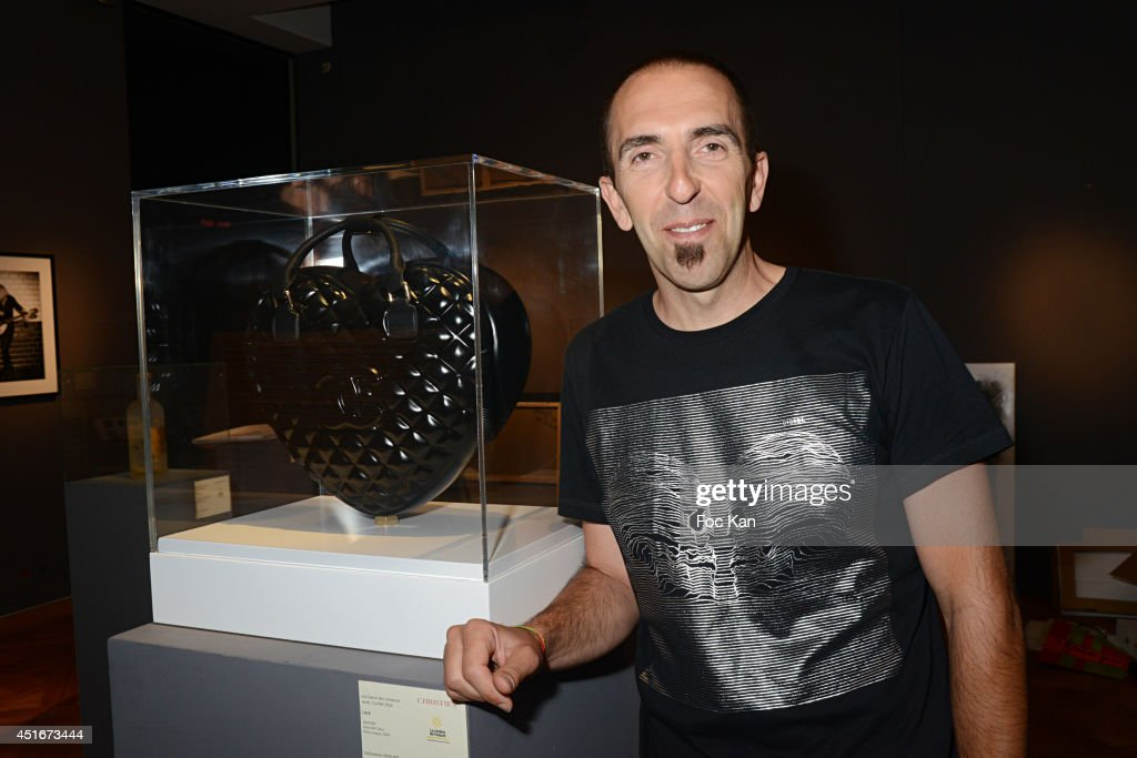 Jak Espi poses with his work during 'Les CÏurs des Createurs' Auction Cocktail in profit of 'La Chaine de L'Espoir' Association at Christie's on July 3, 2014 in Paris, France.
