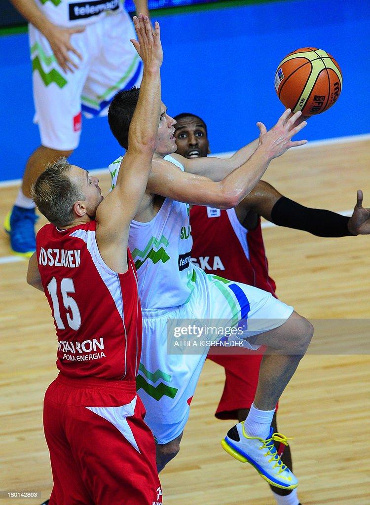 Jaka Lakovic of Slovenia vies with Thomas Kelati and Lukasz Koszarek of Poland during the group C qualification match to EuroBasket 2013...