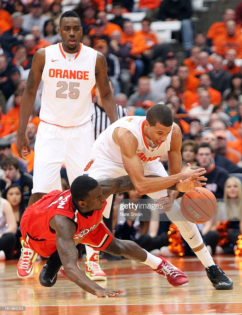 Jakarr Sampson #14 of the St. John's Red Storm dives as he reaches for the ball against Michael Carter-Williams #1 as teamate Rakeem Christmas #25 of the Syracuse Orange looks on during the game at the Carrier Dome on February 10, 2013 in Syracuse, New York.