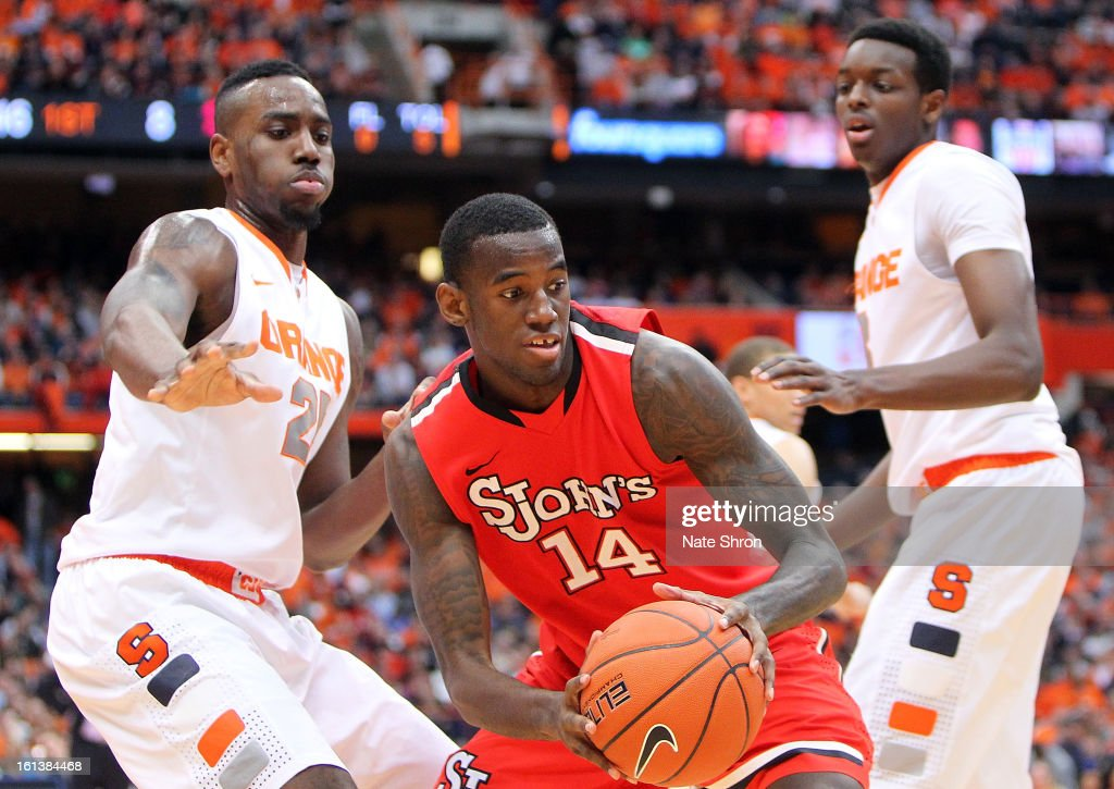 Jakarr Sampson #14 of the St. John's Red Storm holds the ball against Rakeem Christmas #25 and Jerami Grant #3 of the Syracuse Orange during the game at the Carrier Dome on February 10, 2013 in Syracuse, New York.