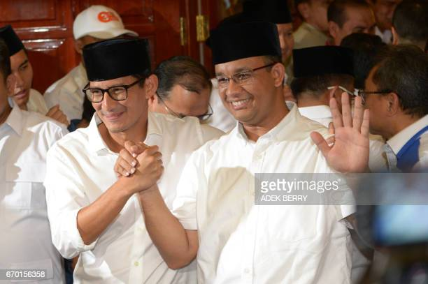 Jakarta governorelect Anis Baswedan and his deputy governorelect Sandiaga Una hold hands during a press conference in Jakarta on April 19 2017...