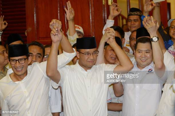 Jakarta governorelect Anis Baswedan his deputy governorelect Sandiaga Una and Hary Tanoe of the Perindo party hold hands together during a press...