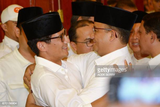 Jakarta governorelect Anis Baswedan hugs his deputy governorelect Sandiaga Una during a press conference in Jakarta on April 19 2017 Jakarta's...