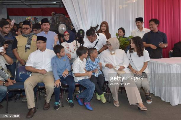 Jakarta governorelect Anis Baswedan sits with his family during a press gathering in Jakarta on April 19 2017 Jakarta's Christian governor on April...