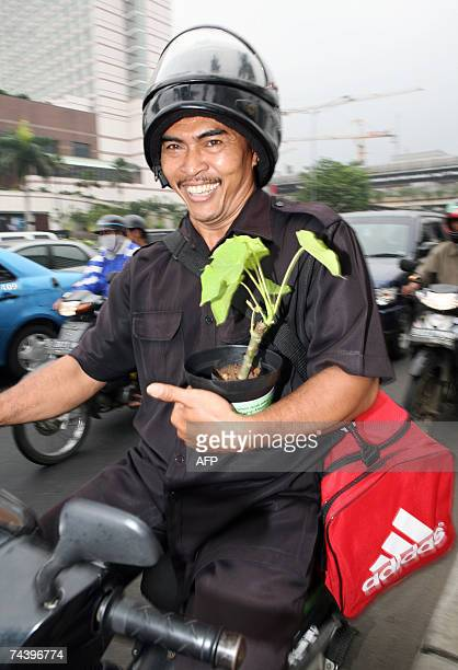 A motorist smiles after receiving a free plant distributed by students at an intersection in Jakarta 05 June 2007 to mark the World Environment Day...