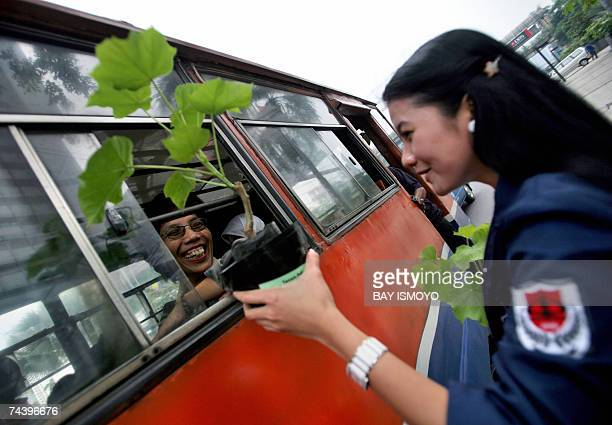 A student distributes free plants at an intersection in Jakarta 05 June 2007 to mark the World Environment Day Indonesia is particularly vulnerable...