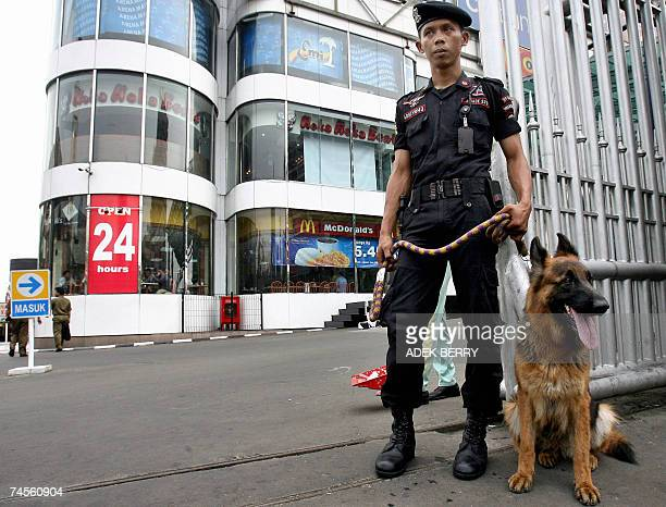 An Indonesian private security personnel and his dog guard a shopping mall in Jakarta 12 June 2007 After a series terrorists attacks in Indonesia...