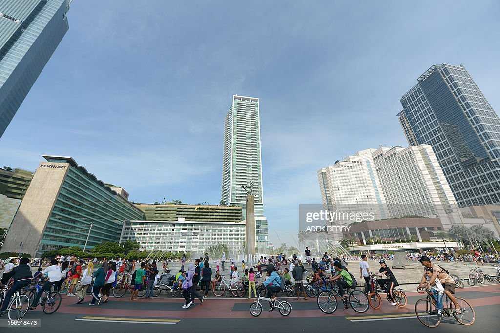 Jakarta residents cycle and sit on the side of a road during car-free day in Jakarta on November 25, 2012. Car free day began in 2007 and is held in Jakarta's main avenues to reduce the number of vehicles on the roads, allowing residents to enjoy their activities along a street which usually congested with vehicles during the week.