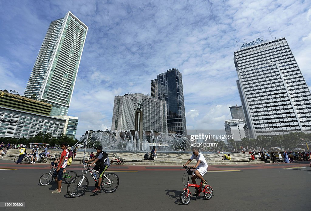 Jakarta residents cycle at the Hotel Indonesia (HI) roundabout on a sunny day in Jakarta on January 27, 2013. Indonesian authorities used generators and cloud-seeding measures to defuse and push away rain-laden clouds to avoid more flooding that has paralysed Jakarta, an official said. The weather agency has forecast heavy rain for January 26-28, raising concerns that Jakarta -- which combined with its satellite cities is home to 20 million people -- may get submerged again. AFP PHOTO / ADEK BERRY