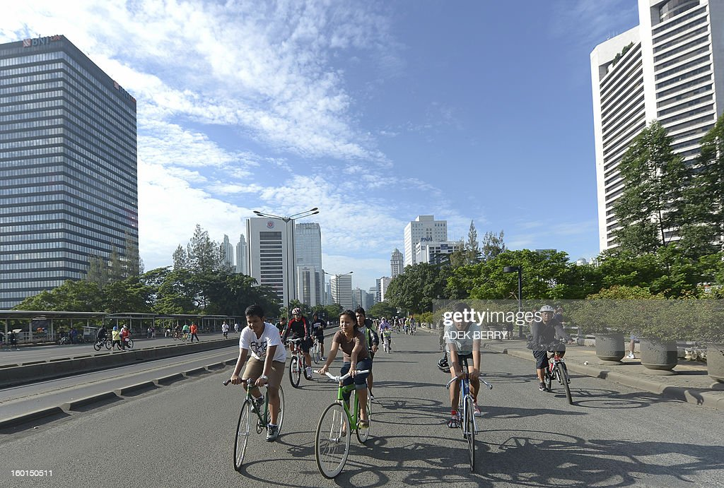 Jakarta residents cycle at the Sudirman main street during a sunny day in Jakarta on January 27, 2013. Indonesian authorities used generators and cloud-seeding measures to defuse and push away rain-laden clouds to avoid more flooding that has paralysed Jakarta, an official said. The weather agency has forecast heavy rain for January 26-28, raising concerns that Jakarta -- which combined with its satellite cities is home to 20 million people -- may get submerged again. AFP PHOTO / ADEK BERRY
