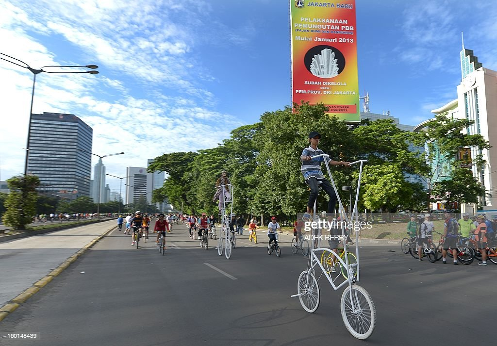 Jakarta residents cycle at the Sudirman main street on a sunny day in Jakarta on January 27, 2013. Indonesian authorities used generators and cloud-seeding measures to defuse and push away rain-laden clouds to avoid more flooding that has paralysed Jakarta, an official said. The weather agency has forecast heavy rain for January 26-28, raising concerns that Jakarta -- which combined with its satellite cities is home to 20 million people -- may get submerged again. AFP PHOTO / ADEK BERRY