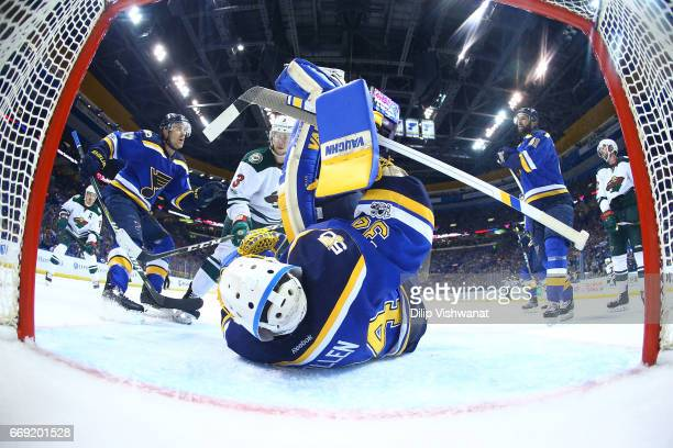 Jake Allen of the St Louis Blues makes a save against Charlie Coyle of the Minnesota Wild as Jaden Schwartz and Robert Bortuzzo of the St Louis Blues...