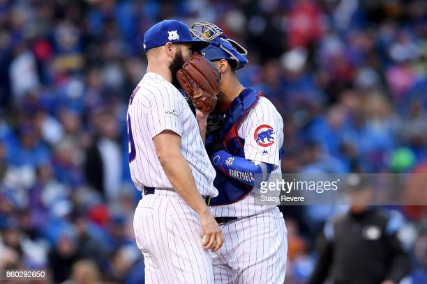 Jake Arrieta and Willson Contreras of the Chicago Cubs meet in the third inning during game four of the National League Division Series against the...