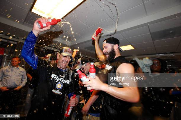 Jake Arrieta of the Chicago Cubs celebrates with catching coach Mike Borzello in the clubhouse after winning Game 5 of the National League Division...