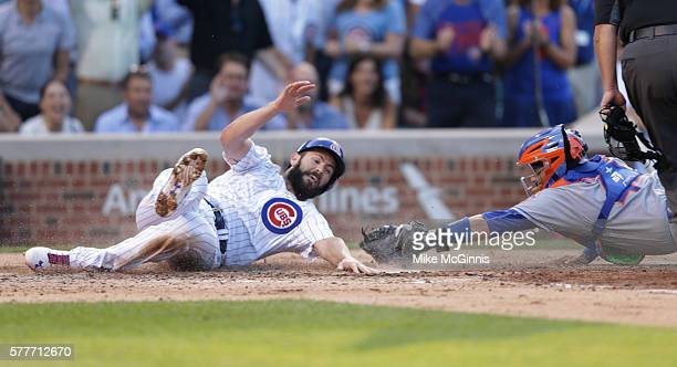 Jake Arrieta of the Chicago Cubs is tagged out by Rene Rivera of the New York Mets during the fourth inning at Wrigley Field on July 19 2016 in...