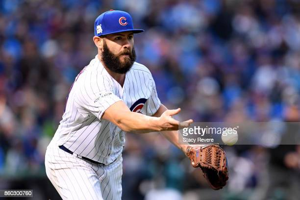 Jake Arrieta of the Chicago Cubs tosses the ball to first base in the fourth inning during game four of the National League Division Series against...