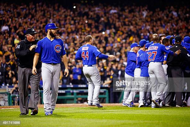 Jake Arrieta of the Chicago Cubs walks off the field with umpire Hunter Wendelstedt after being hit by a pitch thrown by Tony Watson of the...