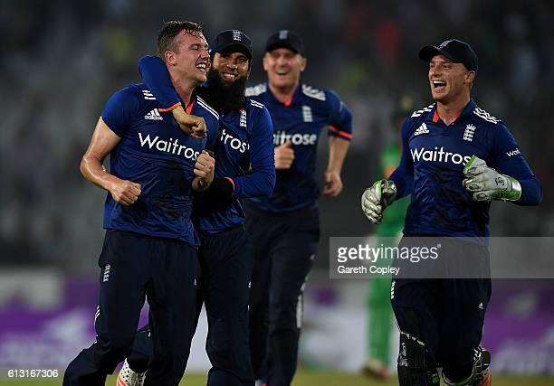 Jake Ball of England celebrates with Moeen Ali and captain Jos Buttler after taking the final wicket of Taskin Ahmed of Bangladesh to win the 1st One...