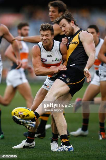 Jake Batchelor of the Tigers kicks the ball as Rhys Palmer of the Giants bumps him during the round 19 AFL match between the Richmond Tigers and the...