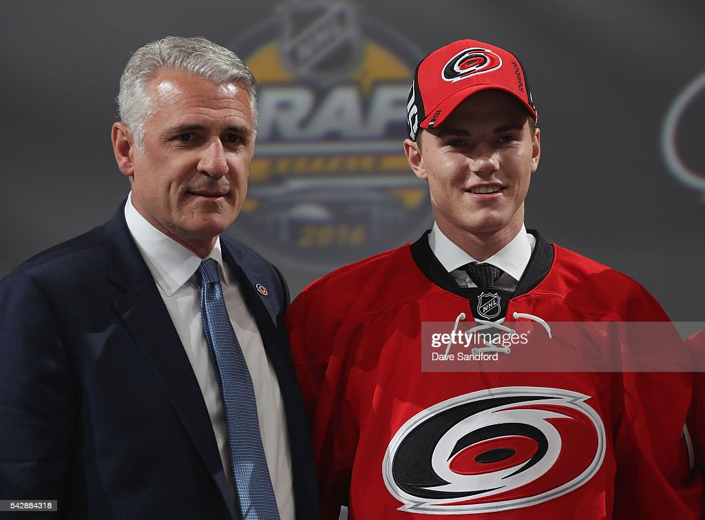 Jake Bean stands onstage with general manager Ron Francis (L) after being selected 13th overall by the Carolina Hurricanes during round one of the 2016 NHL Draft at First Niagara Center on June 24, 2016 in Buffalo, New York.