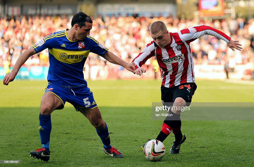Jake Bidwell of Brentford is tackled by Joe Devera of Swindon Town during the npower League One Play Off Semi Final: Second Leg match between Brentford and Swindon Town at Griffin Park on May 6, 2013 in Brentford, England.