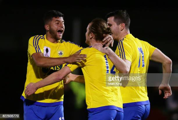 Jake Bradshaw of the Bankstown Berries celebrates with team mates after scoring the first goal during the FFA Cup round of 32 match between Bankstown...