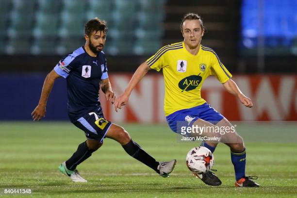 Jake Bradshaw of the Berries is challenged by Michael Zullo of Sydney during the round of 16 FFA Cup match between the Bankstown Berries and Sydney...