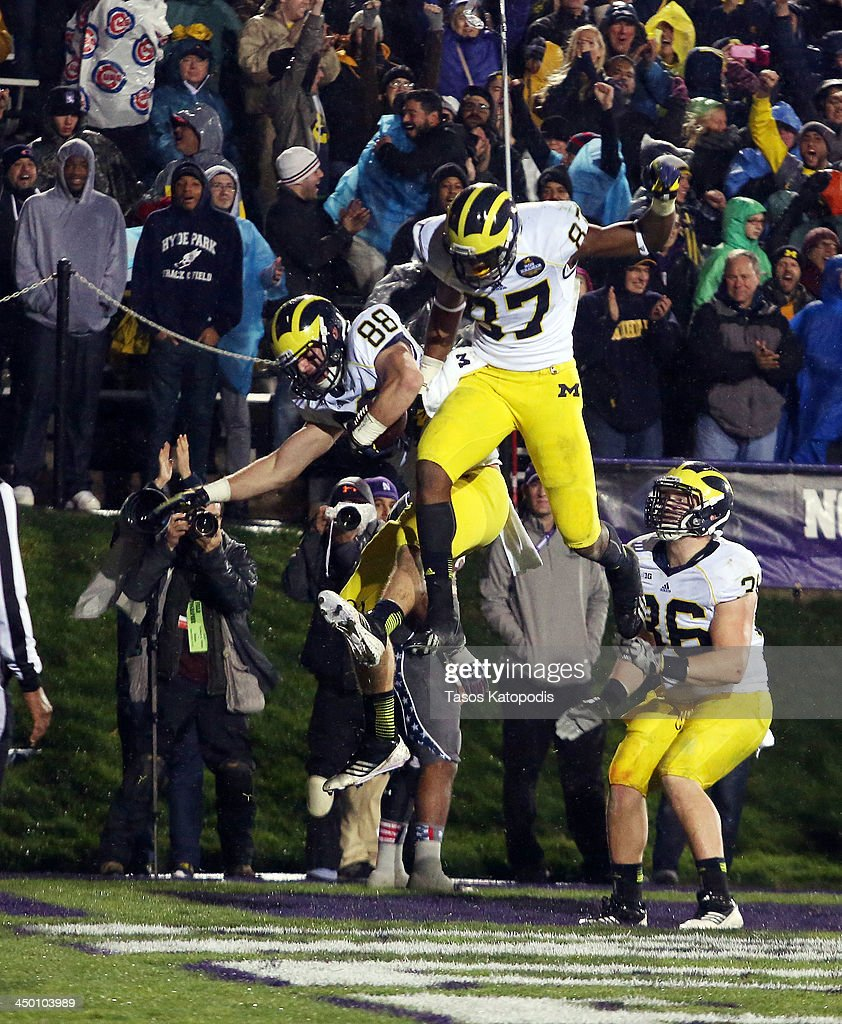 Jake Butt #88 celebrates his touchdown with teammate Devin Funchess #87 of the Michigan Wolverines during play in overtime against the Northwestern Wildcats at Ryan Field on November 16, 2013 in Evanston, Illinois.