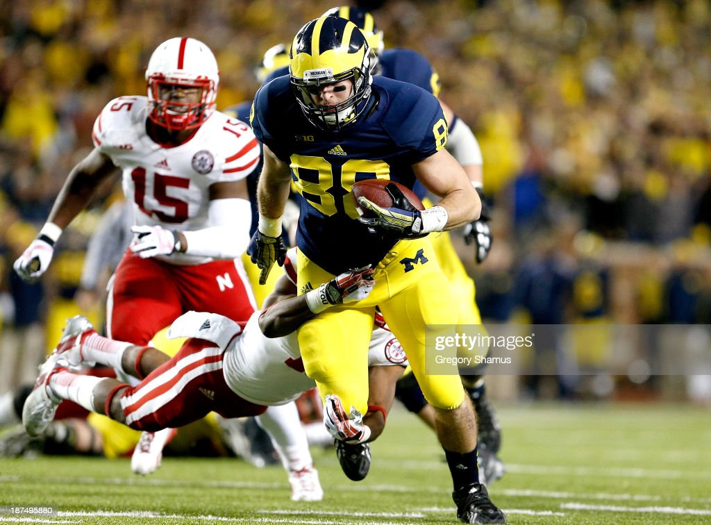 Jake Butt #88 of the Michigan Wolverines breaks a tackle by Andrew Green #11 of the Nebraska Cornhuskers in the third quarter on the Wolverines' first scoring drive at Michigan Stadium on November 9, 2013 in Ann Arbor, Michigan.