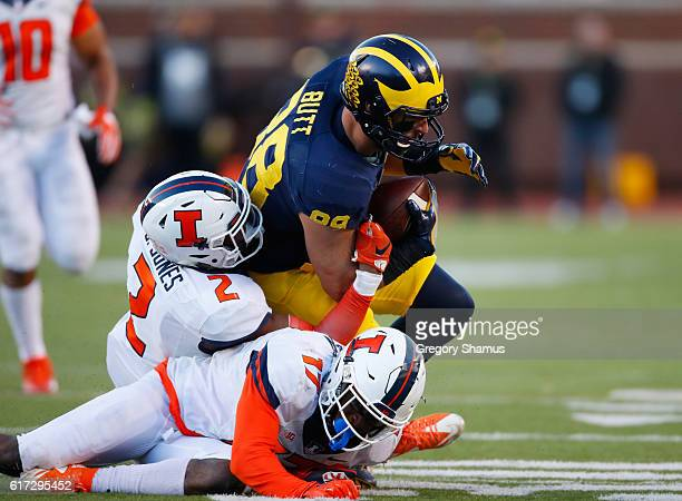 Jake Butt of the Michigan Wolverines is tackled after a third quarter catch by Julian Jones and Stanley Green of the Illinois Fighting Illini on...