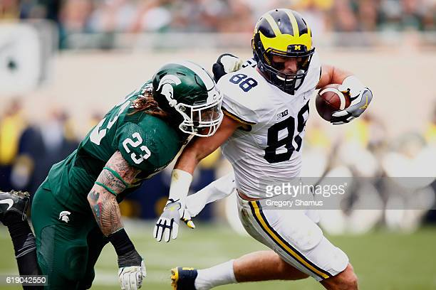 Jake Butt of the Michigan Wolverines looks to get around the tackle of Chris Frey of the Michigan State Spartans after a third quarter catch at...